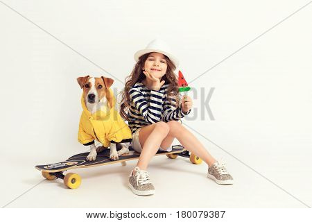 Smiling girl is siting with her dog Jack-Rassel terier breed on their skateboard and holding a lollipop watermelon shaped. An image is taken at the studio with white background.