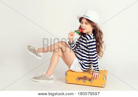Pretty well-dressed girl is sitting on a yellow suitcase with crossed legs and licking a watermelon lollipop. Picture is taken at studio and has white background. Summer vacation, travel, tourism concept