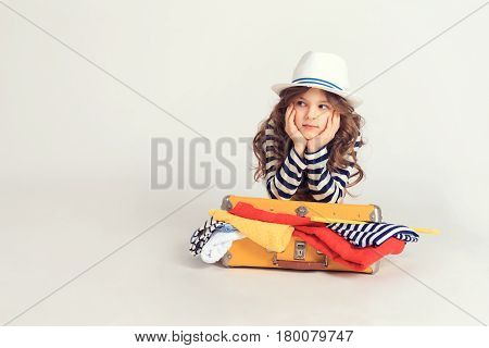 Pretty girl is laying on her filled with coloful clothes suitcase and holding her chin. The picture is taken at studio and has white background.