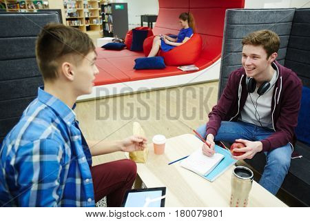Portrait of two teenage boys talking, discussing schoolwork at table of modern student lounge, with girl resting on bean bag in background