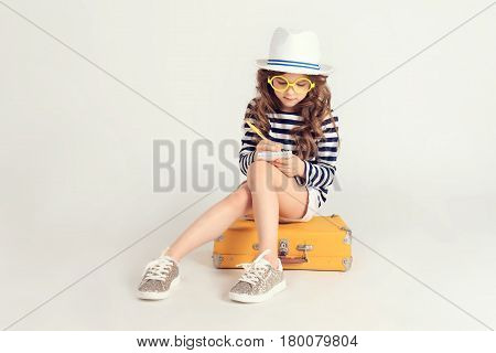 Pretty girl in yellow glasses is writing something in her notebook. She is sitting on a suitcase. The picture is taken at studio and has white background.