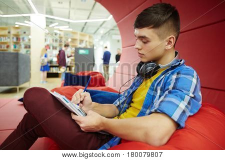 Portrait of  handsome young man studying in creative workspace of modern college,  resting on bean bag and writing in notebook