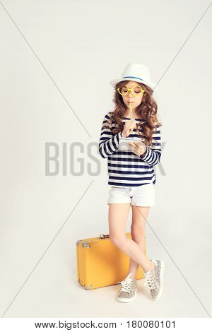 Serious young girl is standing by her yellow suitcase and thinking about something. The picture is taken at studio and has white background