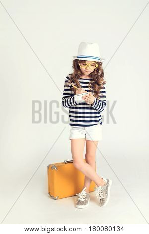 A serious young girl is putting down some marks in her notebook and standing near her yellow suitcase. The picture is taken at studio and has white background.