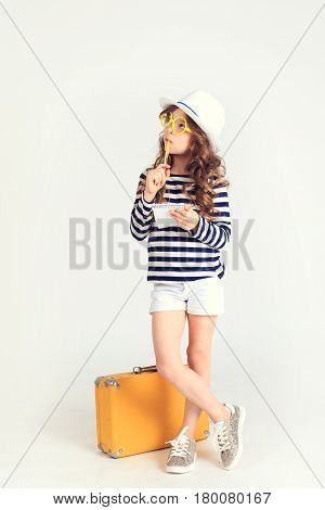 Young serious lady is thinking  and focusing on something. She is standing by her suitcase. The picture is taken at studio and has white background