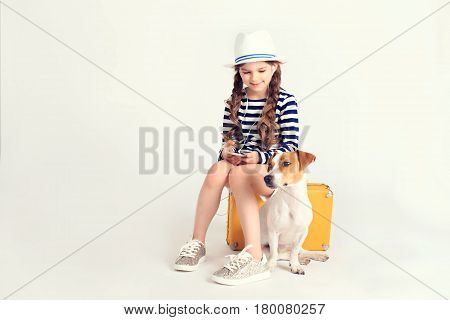 Young nice girl is sitting on a yellow suitcase and listening to music through earphones on smartphone. There is also a dog Jack-Rassel terrier next to her. Travel, tourism, vacation, listening music concept