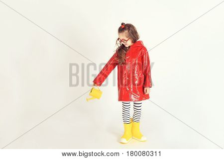 A young girl wearing raincoat and rubber boots is pouring water from watering can on invisible plant. The picture is taken at studio and has white background. Childhood, fashion, imagination concept