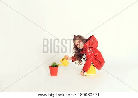 A sitting little girl in red raincoat and rubber boots is watering grass from a pot by using watering can. The picture is taken at studio and has white background