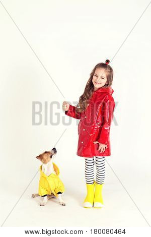 Pretty girl in red raincoat and rubber boots is standing with her dog Jack-Rassel terrier which is wearing yellow raincoat. Kid is holding in hand something invisible. Childhood, fashion, imagination, friendship concep