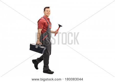 Full length portrait of a plumber with a toolbox and a plunger walking and looking at the camera isolated on white background