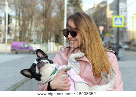 Girl Carries A French Bulldog As A Small Child