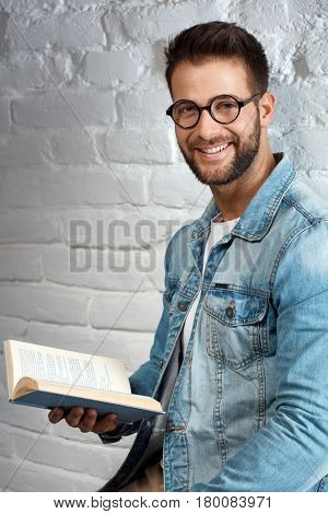 Happy smart casual man in glasses reading book, smiling.