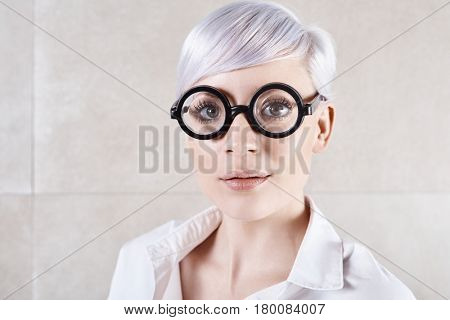Closeup photo of retro woman with lilac hair and glasses.