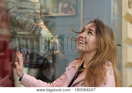 Girl Touches The Glass Showcase Of The Women's Clothing Store
