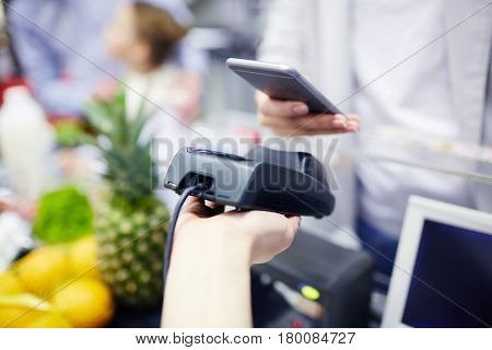 Buyer paying by nfc system for food products in supermarket