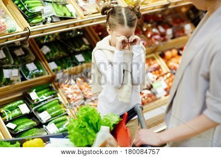 Girl crying on background of supermarket-shelf in front of her mother