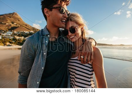 Loving Young Couple Walking On Beach
