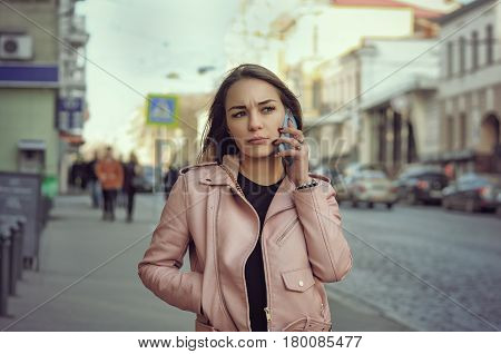 Attractive Girl Talking On The Phone While Walking On The Sidewalk