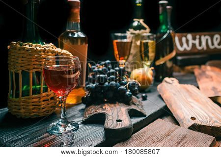 Counter of wine shop with various wine and brandy bottles, wineglasses and fresh fruit. Wooden signboard with text 'Wine'. Retro style