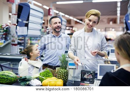 Happy young customer with plastic-card looking at cashier by supermarket checkout