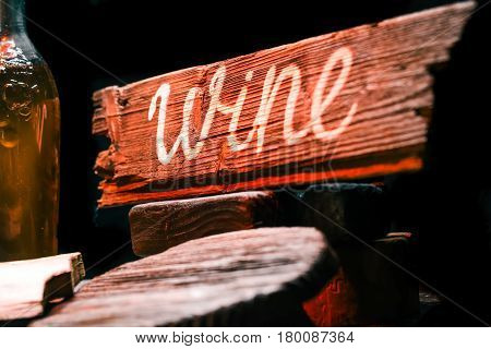 Counter of wine shop with various wine and brandy bottles, wineglasses. Wooden signboard with text 'Wine'. Close-up view
