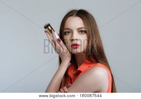 Girl Holding A Brush For Blush In Her Hand, Pressing It To His Cheek