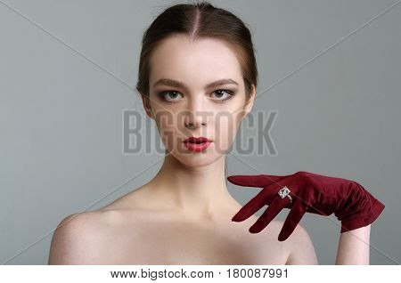Close-up Portrait Of A Beauty Girl With Bare Shoulders In A Red Glove