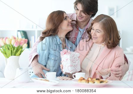 Adult children congratulate the elderly mother on the holiday