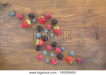 Top view berries: raspberries blueberries blackberries strawberries. Mix of fresh berries on rustic wooden background. Berries on Wooden Background. Summer or Spring Organic Berry over Wood.