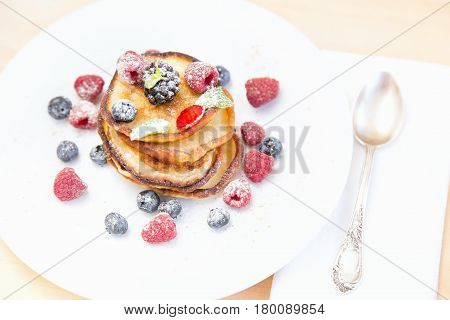 Fluffy pancakes stack with fresh berries and honey. Stack of pancakes with fresh strawberries blueberries raspberries maple syrup and honey for breakfast selective focus.