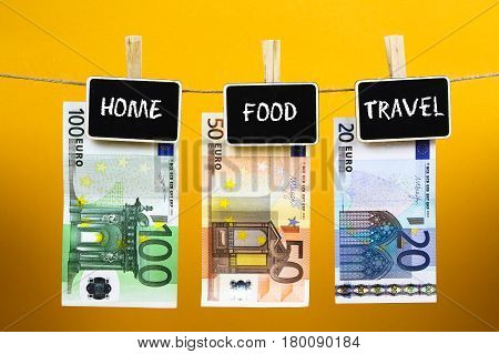 Bank Notes Suspended With Pins With Words - Home Food Travel - Written On A Slate