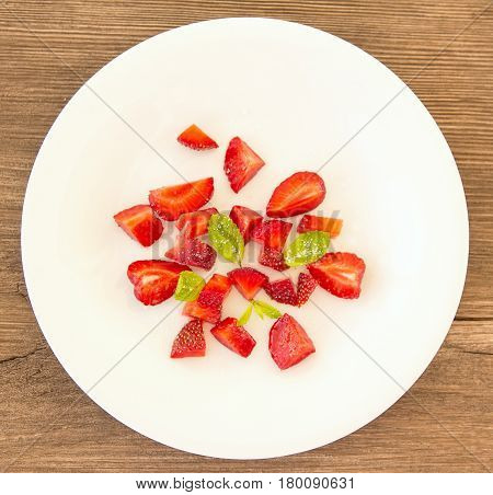 Sliced strawberries on white plate with sugar and mint. Close-up of sliced strawberries. Plate of sliced strawberries on a wooden background.