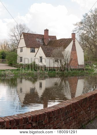 A Lovely Old Cottage In The Glorious Daylight Reflected In The River
