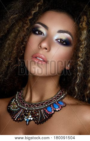 A young African-American girl with creative makeup and small curls. A beautiful model with perfect skin and a pendant made of stones around neck. Beauty of the face. Photo taken in studio. Dark skin.