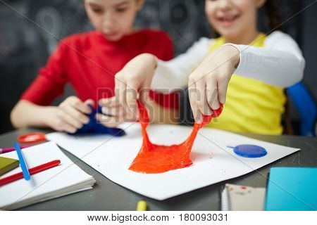 Human hands pulling red slime during play