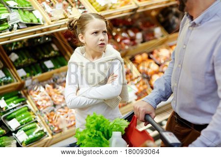 Capricious child asking her father to buy something tasty in supermarket