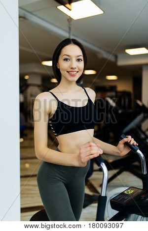 Young Fit Woman Using An Elliptic Trainer In A Fitness Center And Smiling. Portrait Of Fitness Girl