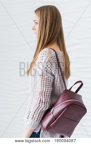Caucasian beautiful girl with long brown hair in grey pullover with backpack of marsala color.