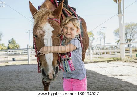 Lovely girl hugging her horse. Horse and jockey small - cute little girl in pink pants with a helmet and her best friend