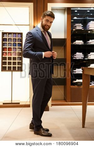 Full length portrait of smiling man in suit standing in a shop and looking at camera. Vertical image