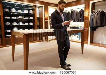 Full length portrait of a bearded man in suit standing in a shop and  using smartphone