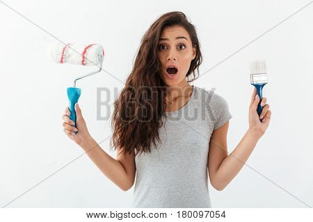 Amazed shocked young woman holding brush and paint roller over white background