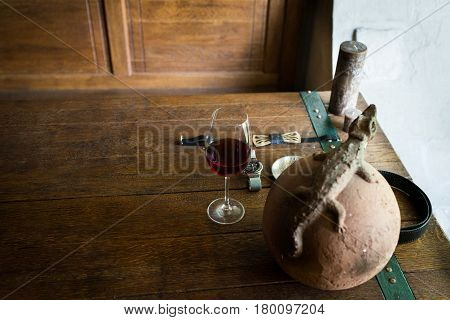 A glass of red wine on the wooden table. Men's accessorizes