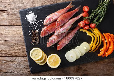 Raw Fish Red Mullet With Vegetable Ingredients And Spices Close-up. Horizontal Top View