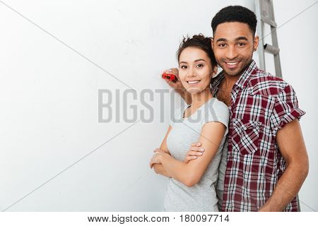 Portrait of happy multiethnic young couple standing together over white background