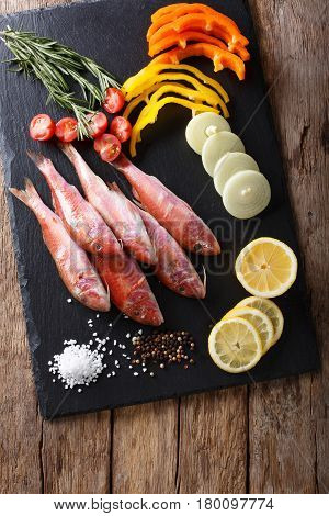 Raw Fish Red Mullet With Vegetable Ingredients And Spices Close-up. Vertical Top View