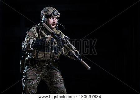 Officer with bulletproof vest and rifle in hands on dark background