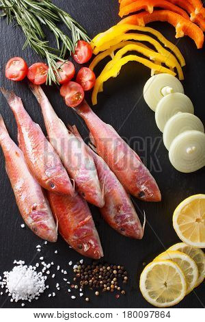 Raw Fish Red Mullet With Ingredients Close-up On The Table. Vertical Top View