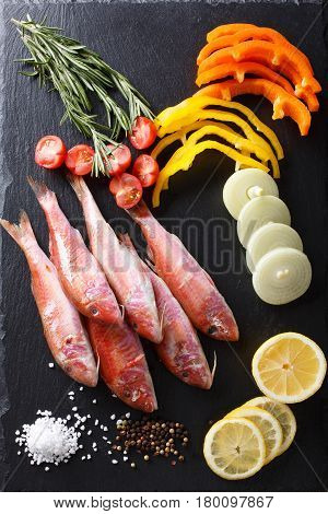 Raw Fish Red Mullet With Vegetables And Lemon On The Table. Vertical Top View