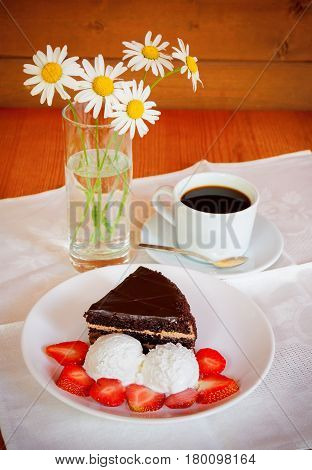 Chocolate cake with ice cream and cup of coffee. Selective focus